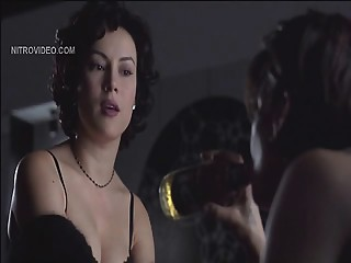 Jennifer Tilly pulling down her bra to show lots of