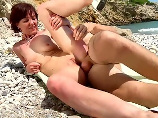 Young stallion fucks a mature pussy on the beach